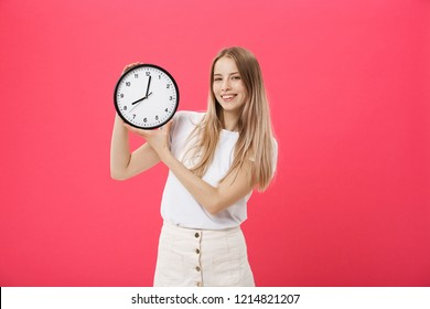 Portrait of an excited young girl dressed in white t-shirt pointing at alarm clock and looking at camera isolated over pink background