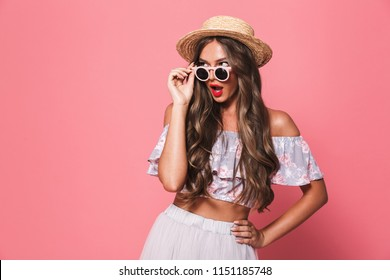 Portrait of an excited young girl in summer clothes looking at copy space over pink background