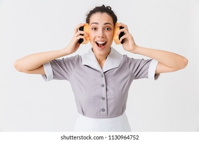 Portrait of an excited young housemaid dressed in uniform using sponges as headphones isolated over white background