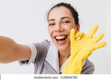 Portrait of an excited young housemaid dressed in uniform and rubber gloves showing ok gesture while taking a selfie isolated over white background