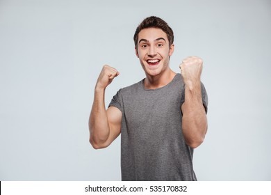 Portrait of an excited young man celebrating success with two fists in the air isolated on the gray background
