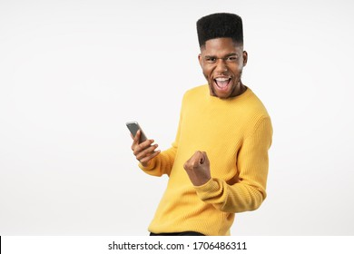 Portrait of excited young man with mobile phone isolated over white background and celebrating