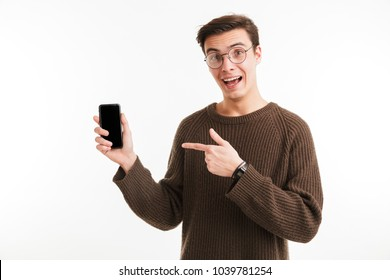Portrait of an excited young man in sweater pointing finger at blank screen mobile phone isolated over white background