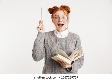 Portrait of an excited young school nerd girl holding book and pointing up isolated over white background