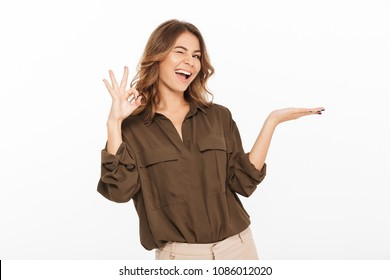 Portrait of an excited young woman holding copy space on her palm and showing ok gesture isolated over white background