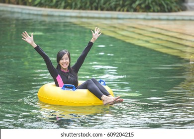 portrait of excited young woman raised her arm enjoy tubing at lazy river pool