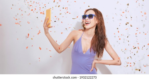 Portrait of an excited young woman taking a selfie under confetti rain isolated over white background