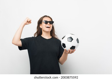 Portrait of excited ypoung woman wearing black tshirt and sunglasses, screaming celebrating team success holding football
