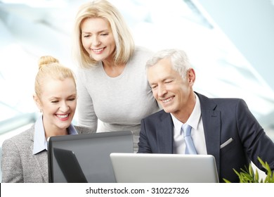 Portrait of executive businessman sitting with businesswomen and consulting. Business people working together on laptop while sitting at meeting.