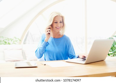 Portrait of executive businesswoman sitting at office desk and using laptop while talking with somebody on mobile phone.