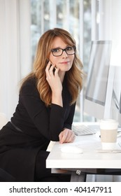 Portrait of an executive businesswoman using a cellphone while sitting at a desk in an office