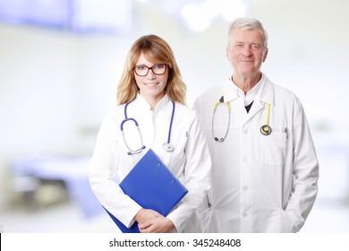 Portrait of executive female doctor holding in her hand a clipboard while senior specialist standing next to her at doctors office.