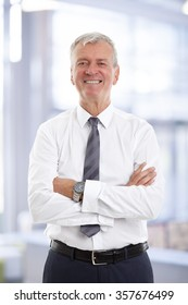 Portrait of executive financial director with arms crossed looking at camera and smiling while standing at office.