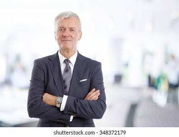 Portrait of executive financial director standing at office with arms crossed while looking at camera.