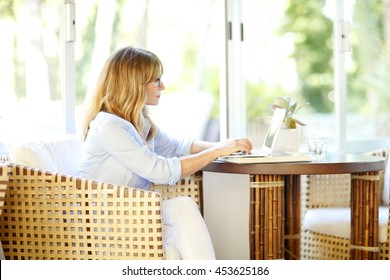 Portrait of executive mature woman typing on laptop while working at home.