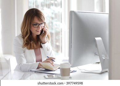 Portrait of and executive middle aged businesswoman sitting in front of computer and making call while working in her office.