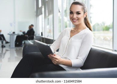 Portrait of an executive professional businesswoman sitting office in casual and working with tablet