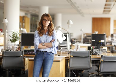 Portrait of an executive professional mature businesswoman sitting on office desk in casual and smiling. Shallow focus.