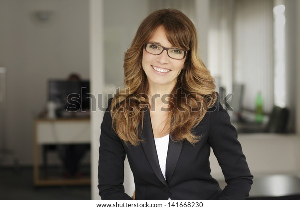 Portrait of an executive professional mature businesswoman sitting in office and smiling. Shallow focus.