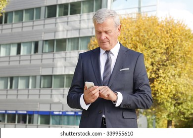 Portrait of executive senior broker standing in front of stock exchange and using his mobile.