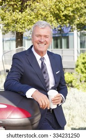 Portrait of executive senior businessman standing at business park and holding in hand a cup of coffee while relaxing after meeting.