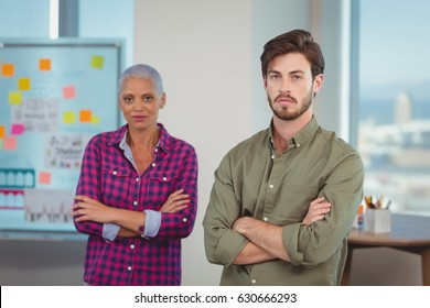 Portrait of executives standing with arms crossed in office