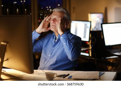 Portrait of exhausted businessman sitting at office in front of computer and holding his head with two hands while working late night.