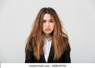 Portrait of an exhausted businesswoman dressed in suit with messy hair looking at camera isolated over gray background