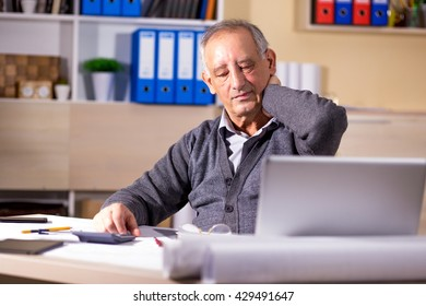 Portrait of exhausted senior businessman working in his office.