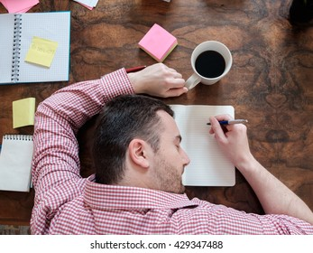 portrait of exhausted worker sleeping on his desktop