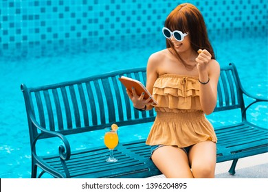 Portrait of an Exited young asians girl looking her mobile phone,smart phone or tablet sit on chair beside swimming pool.