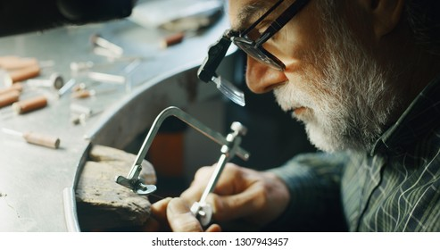 Portrait of experienced goldsmith working on a handmade jewelry bracelet chain of precious metal white gold in a workshop. Concept of jewelry, luxury, goldsmith, gold, silver, precious metals