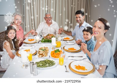 Portrait of an extended family at dining table against snow falling