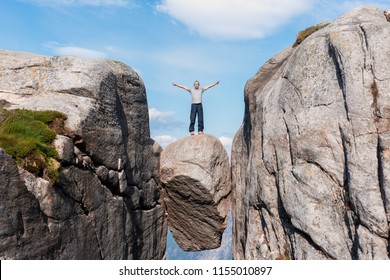 Portrait of a extreme plan travel for the handsome old man on the stone of the kjerag in the mountains kjeragbolten of Norway, the feeling of complete freedom