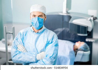 Portrait of eye surgeon in the operating room with patient and laser machine on the background. Laser vision correction