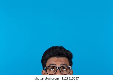 Portrait of eyes looking up wearing glasses hiding behind something on a blue background.