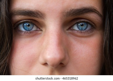 Portrait of the eyes of a white Caucasian young girl with blue eyes and brown hair after bathing in the pool.