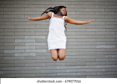 Portrait of a fabulous black african american woman dancing and jumping against brick wall in the background.