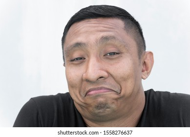 A portrait of the face of an Asian Indonesian male model who smiles and frown awkwardly at the same time AKA frown smile. Portrait on white background.