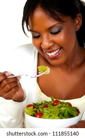 Portrait of the face of a pretty young woman eating green salad on a bowl.