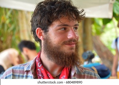 Portrait of face young romantic, charismatic dude. Boy is hippie, rastaman, hobo. Charming sweaty student on hot summer vacation, holiday. Sweat on wet skin. He have middle beard, big nose, neck scarf