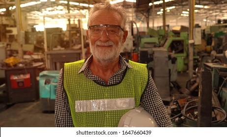 Portrait factory senior man worker on manufacture workshop background