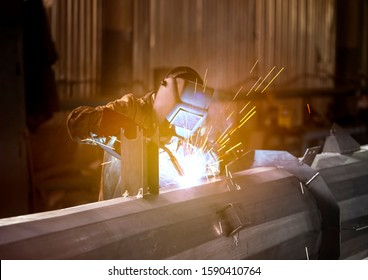 Portrait of a factory welder working at the plant. Metallurgical plant for the production of metal structures. Worker in a welding mask protected from dropping sparks.