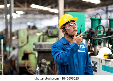 Portrait of factory worker and engineer at industrial facility. Construction worker in hardhat and Walkie-talkie or Two Way Radio in hand