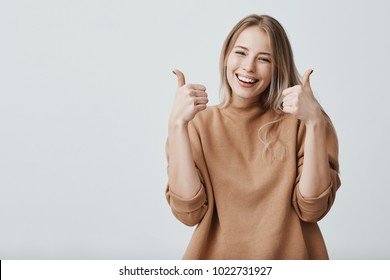 Portrait of fair-haired beautiful female student or customer with broad smile, looking at the camera with happy expression, showing thumbs-up with both hands, achieving study goals. Body language