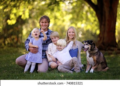 A portrait of a family of 5 blonde haired, caucasian people, sitting outside under the trees with their adopted pet German Shepherd Mix Breed Dog.