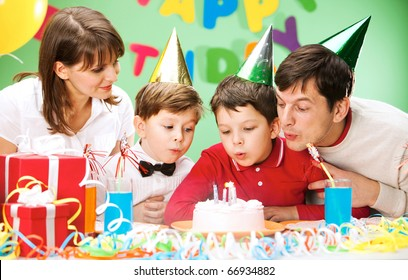 Portrait of family blowing together at the holiday candles on the cake