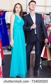 Portrait of family couple posing together in the female clothes shop. Focus on both persons