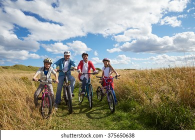 Portrait Of Family Cycling Through Countryside Together