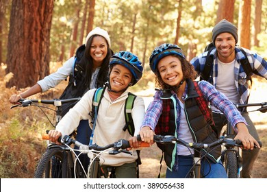 Portrait Of Family Cycling Through Fall Woodland